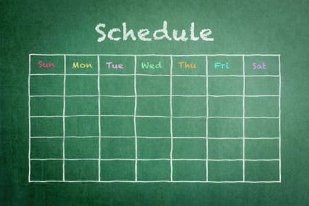 Schedule with grid timetable on green chalkboard