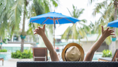 Summer resort hotel stay relaxation of business woman take it easy happily resting on beach chair on holiday travel vacation poolside in peacefully with tropical beach swimming pool