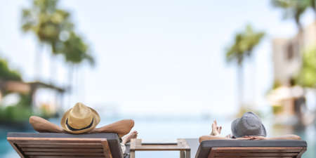 Summer resort hotel stay relaxation with tourist traveller couple take it easy happily resting on beach chair on holiday travel vacation poolside peacefully at tropical beach swimming pool