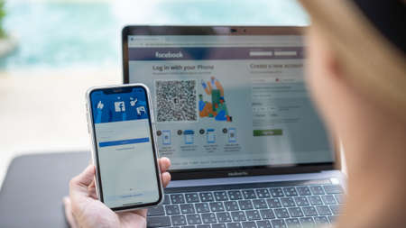 PETCHABURI, THAILAND-MAY 13, 2019: Facebook social media app icon signup page on iphone XR mobile smartphone device and computer laptop for user FB live public communication network.