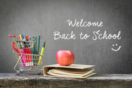 Welcome back to school with shopping cart, school supplies, stationery, notebook, apple on wood table top and black teacher chalkboard