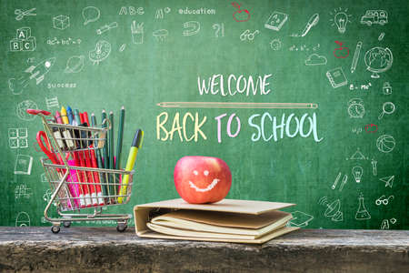 Welcome back to school, educational greeting announcement for students and teacher on green chalkboard with creative kid's doodle drawing and stationary supplies, book and apple Stock Photo - 124855575