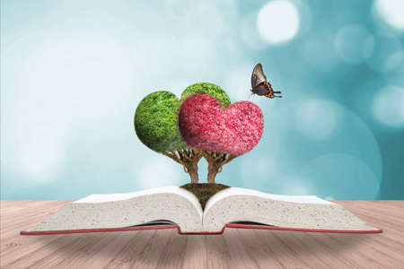 Romantic heart tree couple on love story book on wood deck & greenery natural bokeh background Banco de Imagens