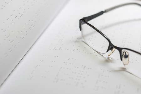 Braille book for low vision/ blind person reading the sign, eyeglasses background.