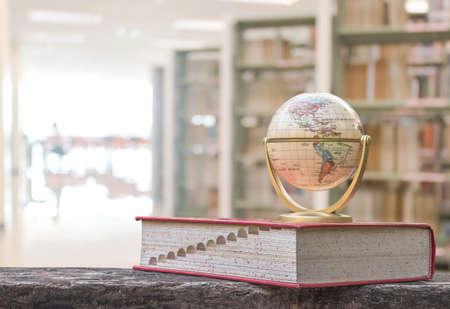 Modèle de globe sur manuel ou dictionnaire sur table dans une bibliothèque scolaire ou universitaire ressource éducative pour la connaissance