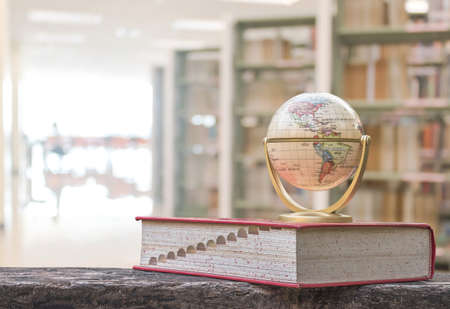 Wereldbolmodel op leerboek of woordenboek op tafel in school- of universiteitsbibliotheek educatief hulpmiddel voor kennis