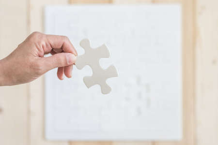 Jigsaw puzzle game piece in persons hand on blur white wood background