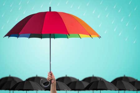 Levensverzekeringsbescherming, zakelijk financieel leiderschapsconcept met de hand van de leider met regenboogparaplu die opvallend uniek is