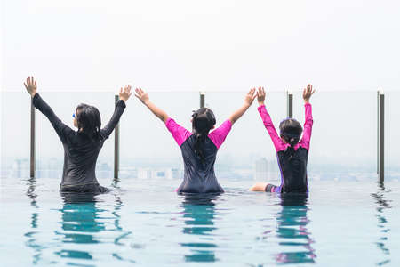 Children friendship concept with happy girl kid group having fun playing together in swimming pool on rooftop hotel or luxury condominium with city infinity skyline view Фото со стока