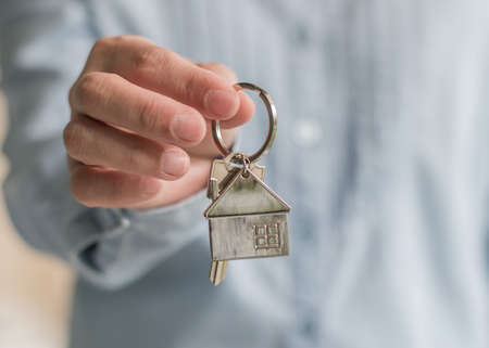 Home buyer or apartment sale agent giving key for leasing, security and ownership concept