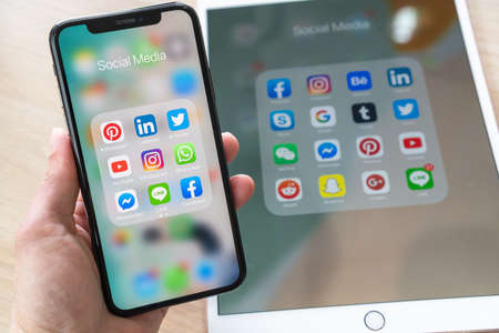 BANGKOK, THAILAND- June 26, 2019: Social media app, mobile cross-channel internet online application for people lifestyle in  multi-channel digital 4.0 age with logo on iPhone X and ipad pro touchscreen Editorial