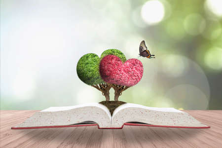Romantic heart tree couple on love story book on wood deck & greenery natural bokeh background Stok Fotoğraf
