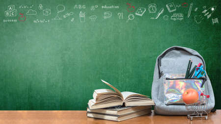 Back to school concept with school books, textbooks, backpack and stationery supplies on classroom desk with teachers green chalkboard background with educational doodle for new academic year begin