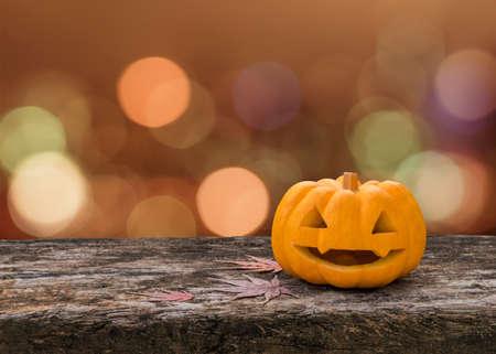 Halloween pumpkin Jack OLantern happy face on wood table with orange bokeh background
