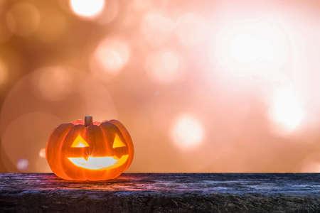 Halloween pumpkin Jack OLantern happy smiling face on grunge wood and autumn sun flare