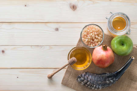 Rosh Hashanah (Hashana)  (jewish New Year holiday) and Yom Kippur concept with Ram shofar (horn) and traditional food, apple, honey, pomegranate fruit flat lay on wood table background from top view