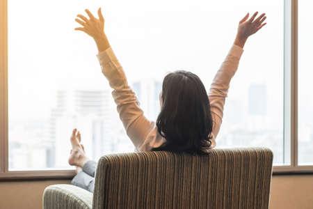 Concept de qualité de vie avec vue arrière d'une femme d'affaires relaxante assise au repos sur un fauteuil confortable dans une chambre d'hôtel moderne ou un salon de maison de luxe regardant vers la belle scène urbaine de la ville