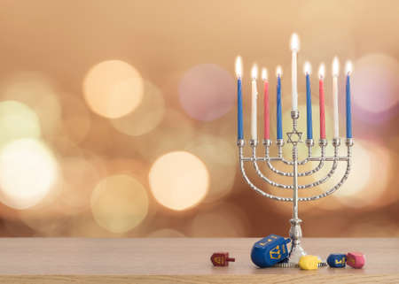 Hanukkah Jewish holiday background with menorah (Judaism candelabra)  burning candles and traditional Dreidrel game toy on wood table and on autumn bokeh sun flare Stok Fotoğraf