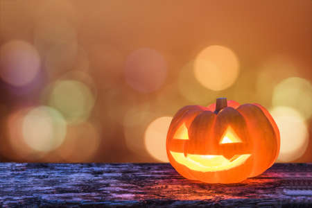 Halloween pumpkin orange Jack OLantern happy smiling face on grunge wood candle light lit bokeh for halloween party autumn holiday celebration decoration