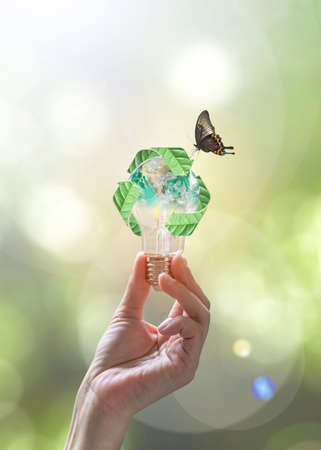 Ecology, energy saving, renewable, waste management and sustainable development concept with lightbulb with recycle leaves environmental protection symbol in people hand