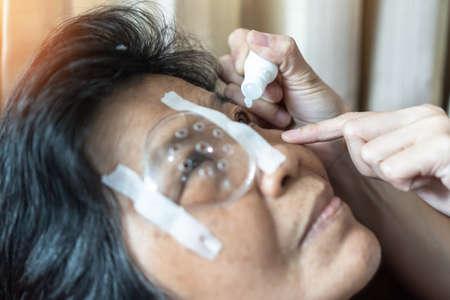 Elderly patient woman having eye drop care on Age-related eye diseases, AMD, Diabetic retinopathy, Glaucoma, low vision, dry eyes