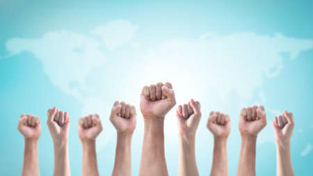 International human rights or labor day with Hands with clenched fist of people crowd (men and women) isolated on world map and sky background