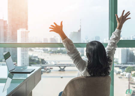 L'équilibre travail-vie personnelle, le travail accompli et le concept de célébration du succès avec une femme heureuse se reposent tranquillement dans un hôtel d'affaires de luxe ou au bureau à domicile avec un ordinateur portable sur le bureau