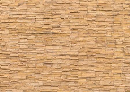 Mur de tuiles en brique de pierre de roche texture de fond détaillé en couleur marron jaune