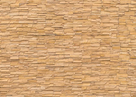 Rock stone brick tile wall aged texture detailed pattern background in yellow brown color