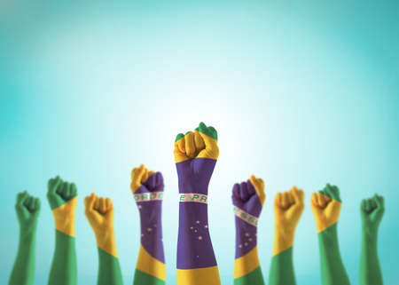 Brazil flag on people hands with clenched fists raising up for labor day, republic proclamation day, national holiday celebration and stay strong for Brazilian power isolated on blue sky background. 版權商用圖片