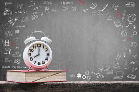 Back to school education concept with clock on book on black chalkboard 스톡 콘텐츠