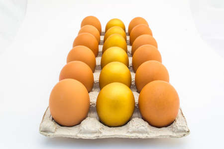 A row of golden eggs on an egg tray