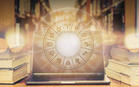 Signo del zodíaco horóscopo astrología y estudio de constelaciones para el concepto de curso de educación de predicción y adivinación con rueda horoscópica sobre libro antiguo y computadora portátil en la biblioteca de la escuela