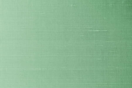 Green background of silk fabric satin texture cotton cloth pattern with shiny gradient silky woven detail