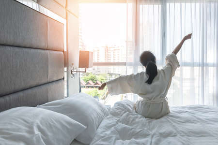 Work-life quality balance concept with lazy lifestyle of Asian girl on bed relaxing in comfort city hotel bedroom, take it easy, resting from good sleep waking up on weekend morning having a good day Banque d'images - 129957136