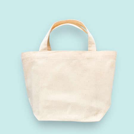 Paño de tela de algodón blanco de lona de bolso de mano para plantilla en blanco de maqueta de saco de compras de hombro ecológico aislado sobre fondo azul pastel (trazado de recorte)