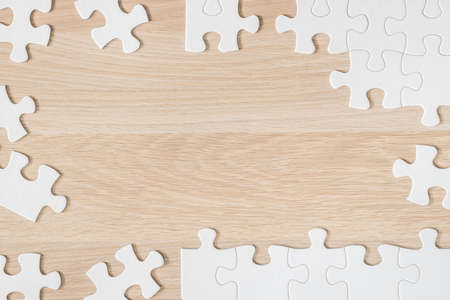 Jigsaw puzzle game piece on light cream brown wood texture background