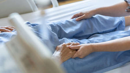 Elderly senior patient (ageing old adult person) lying in hospital bed with family caregiver or caretaker nurse in nursing hospice, geriatrician palliative home having  medical health care service