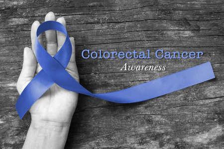 Darm- oder Dickdarmkrebsbewusstsein mit dunkelblauem Band zur Hand auf altem Holz
