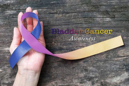 Bladder cancer awareness marigold blue purple  ribbon color splashed on helping hand, old aged background