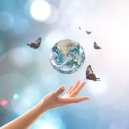 World environment day, ecology and ozone layer protection concept with woman's hand supporting earth planet under sun light flare with beautiful butterfly
