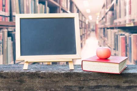 Bildungskonzept mit leerem schwarzem Tafelständer für Ankündigung mit Apfel, Lehrbuch auf verschwommenem Hintergrund der Schulbibliothek