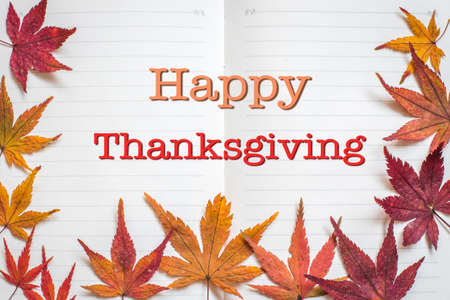 Happy thanksgiving day text message on note book pages with lines and frame of colorful seasonal dry maple leaves