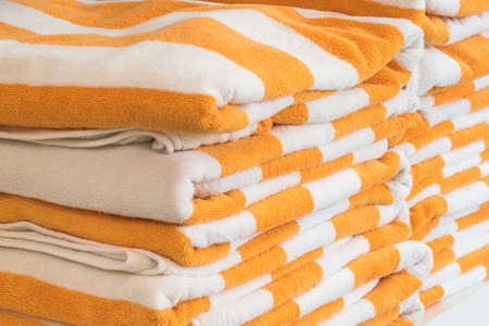 Bath towel rolls fabric texture cloth background in white orange stripe for swimming pool, sea beach, gym fitness in resort hotel