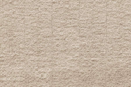 Rustic grunge granite tiled wall detailed pattern texture in natural light beige cream sepia color