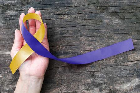 Cinta azul amarilla de concientización sobre la mano amiga para el día mundial del síndrome de down WDSD 21 de marzo recaudando apoyo para pacientes con discapacidad por síndrome de down y síndrome de la salida torácica - (TOS)