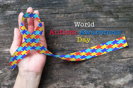 World Autism awareness day with multi-color puzzle ribbon on person's hand