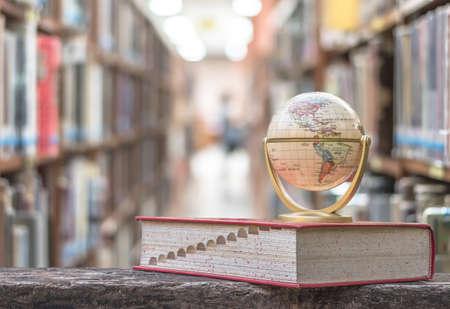 7 FEBBRAIO 2018 - BANGKOK, THAILANDIA: Modello del globo sul libro di testo o dizionario sul tavolo nella risorsa educativa della biblioteca della scuola o dell'università per la conoscenza