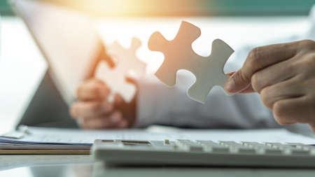 Geschäftslösung und Strategie für das Erfolgskonzept des Unternehmensgeschäfts mit Puzzleteilen in den Händen von Geschäftsleuten, die Problemlösungsideen und strategische Planung finden