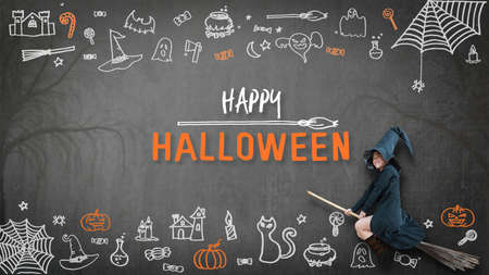 Happy halloween with girl kid in witch costume riding broomstick on spooky dark black chalkboard with chalk doodle of trick or treat candies and scary ghost for holiday greeting festival celebration 写真素材